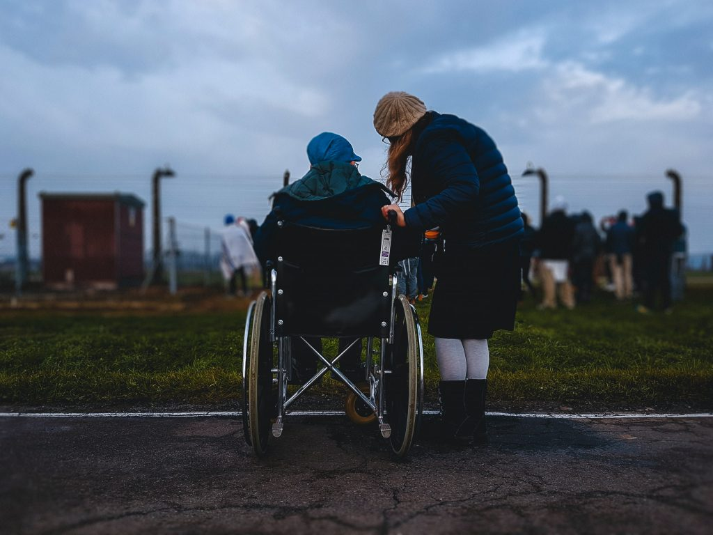 Person helping someone in wheelchair